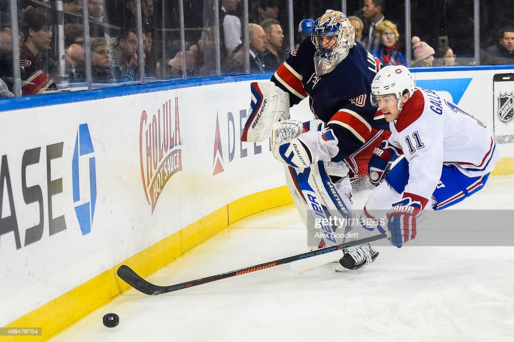 Henrik Lundqvist #30 of the New York Rangers dumps the puck past Brendan Gallagher #11 of the Montreal Canadiens in the first period at Madison Square Garden on November 23, 2014 in New York City.