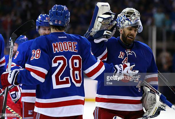 Henrik Lundqvist of the New York Rangers highfives Dominic Moore after defeating the Montreal Canadiens in overtime to win Game Four of the Eastern...