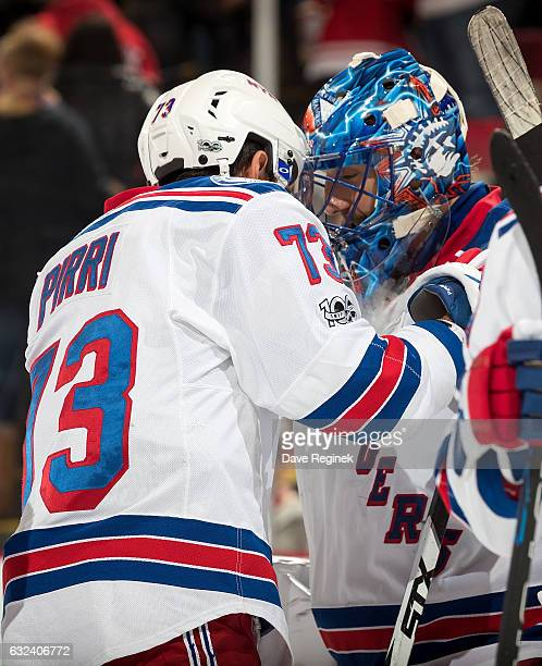 Henrik Lundqvist of the New York Rangers is congratulated by teammate Brandon Pirri for his overtime win following an NHL game against the Detroit...