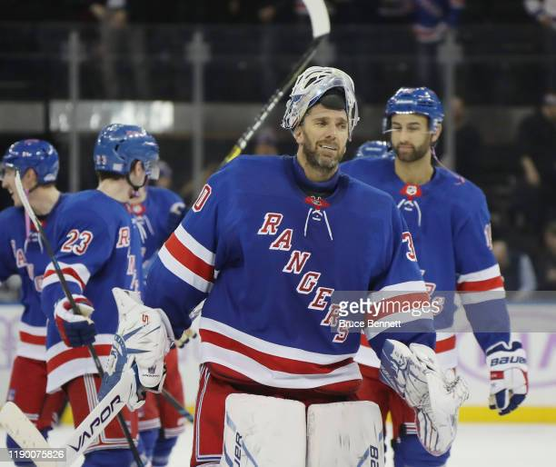 Henrik Lundqvist of the New York Rangers leaves the ice following a 3-2 overtime victory over the Minnesota Wild at Madison Square Garden on November...