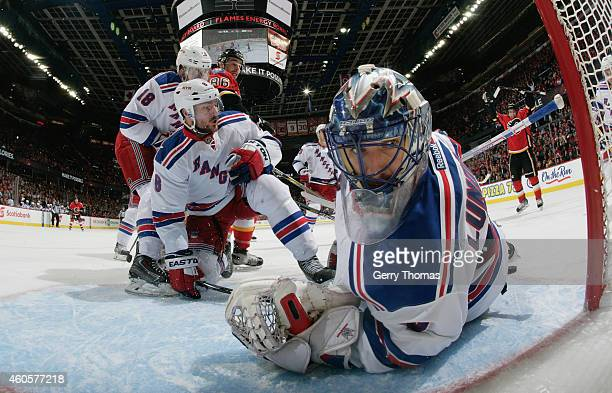 Henrik Lundqvist of the New York Rangers looks back at the puck after a goal by the Calgary Flames at Scotiabank Saddledome on December 16 2014 in...