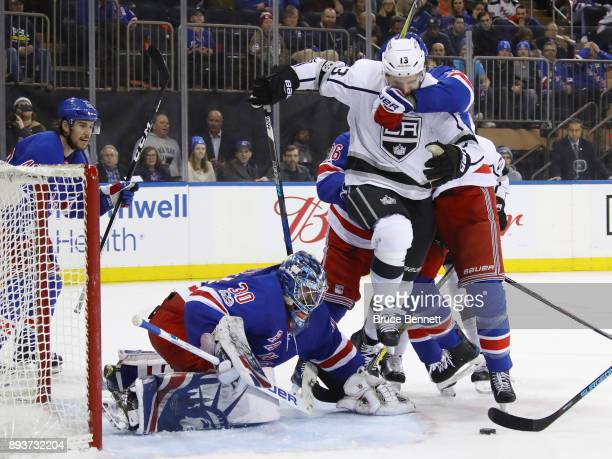 Henrik Lundqvist of the New York Rangers looks to grab the puck as Kyle Clifford of the Los Angeles Kings is held in front of the net during the...