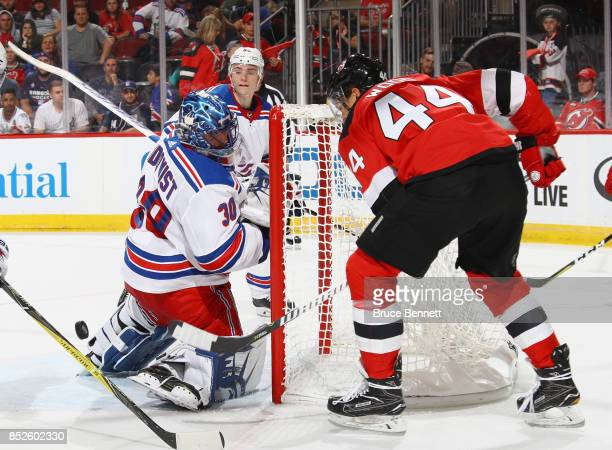 Henrik Lundqvist of the New York Rangers loses sight of the puck as Miles Wood of the New Jersey Devils misses a scoring opportunity during the...