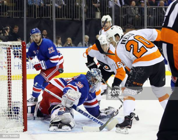 Henrik Lundqvist of the New York Rangers makes a first period save as Jori Lehtera and Taylor Leier of the Philadelphia Flyers converge on the net at...