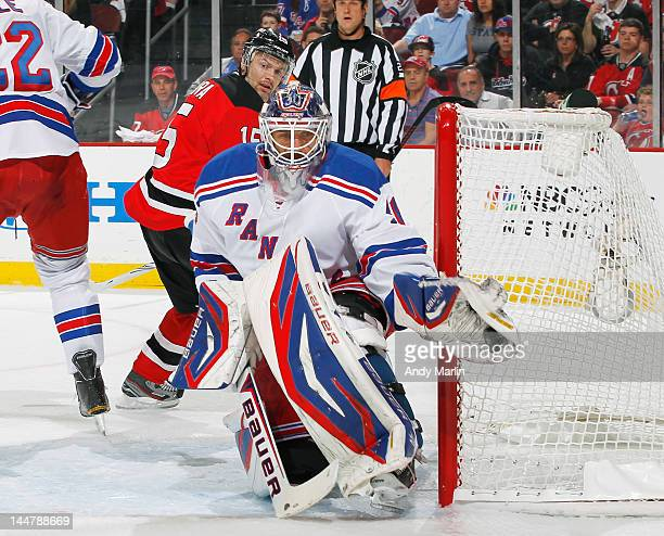 Henrik Lundqvist of the New York Rangers makes a glove save as Petr Sykora of the New Jersey Devils looks for a rebound in Game Three of the Eastern...