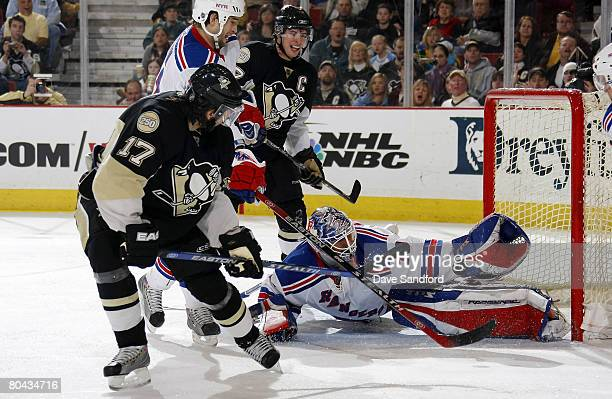 Henrik Lundqvist of the New York Rangers makes a glove save on Petr Sykora of the Pittsburgh Penguins as Sidney Crosby of the Pittsburgh Penguins...