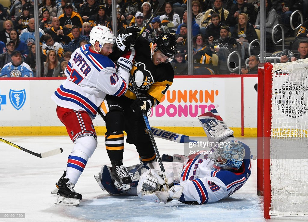 Henrik Lundqvist #30 of the New York Rangers makes a save in front of Riley Sheahan #15 of the Pittsburgh Penguins and Steven Kampfer #47 at PPG Paints Arena on January 14, 2018 in Pittsburgh, Pennsylvania.