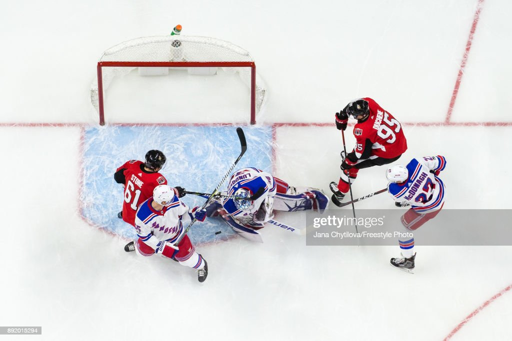 Henrik Lundqvist #30 of the New York Rangers makes one of twenty-six saves as teammates Nick Holden #55 and Ryan McDonagh #27 defend against Mark Stone #61 and Matt Duchene #95 of the Ottawa Senators at Canadian Tire Centre on December 13, 2017 in Ottawa, Ontario, Canada.