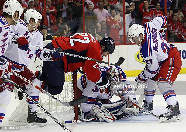 Henrik Lundqvist of the New York Rangers makes the save as Mike Knuble of the Washington Capitals flies past him in Game One of the Eastern...