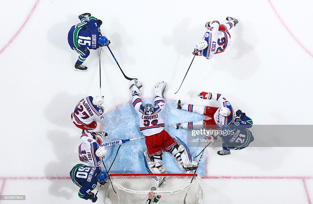 Henrik Lundqvist #30 of the New York Rangers sprawls in a crowd to bat the puck away from Derek Dorsett #15 of the Vancouver Canucks during their NHL game at Rogers Arena November 15, 2016 in Vancouver, British Columbia, Canada. New York won 7-2.