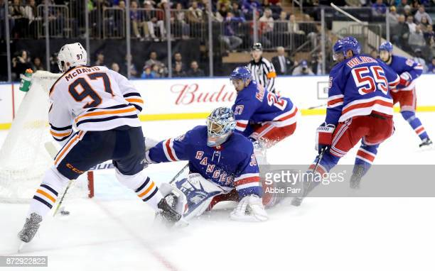 Henrik Lundqvist of the New York Rangers stretches to block a shot against Connor McDavid of the Edmonton Oilers in the third period during their...