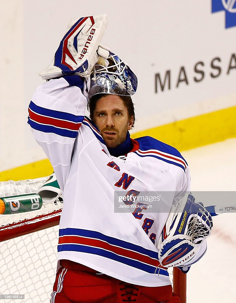 Henrik Lundqvist #30 of the New York Rangers takes his helmet off during a timeout against the Boston Bruins during the season opener game on January 19, 2013 at TD Garden in Boston, Massachusetts.