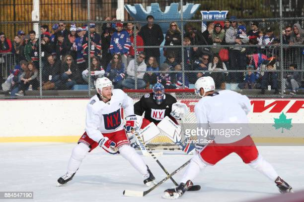 Henrik Lundqvist of the New York Rangers tends the net as Boo Nieves skates against Steven Kampfer during the teams open practice outside at Lasker...