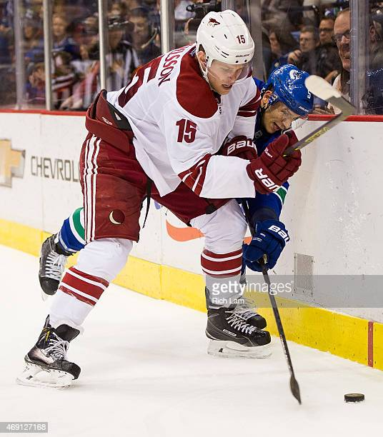 Henrik Samuelsson of the Arizona Coyotes and Luca Sbisa of the Vancouver Canucks battle for the puck along the end boards in NHL action on April 9...