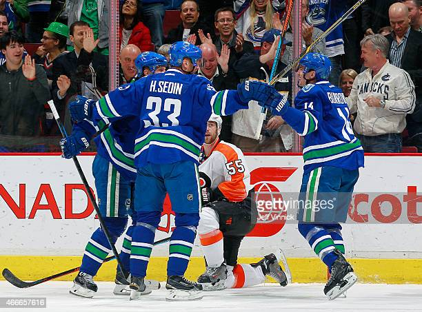 Henrik Sedin and Daniel Sedin congratulate goal scorer Alexandre Burrows of the Vancouver Canucks in front of Nick Schultz of the Philadelphia Flyers...