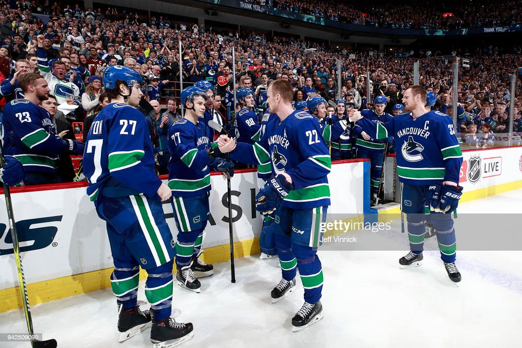 Henrik Sedin #33 and Daniel Sedin #22 of the Vancouver Canucks congratulate teammates after their NHL game against the Arizona Coyotes at Rogers Arena April 5, 2018 in Vancouver, British Columbia, Canada. Vancouver won 4-3 in overtime.