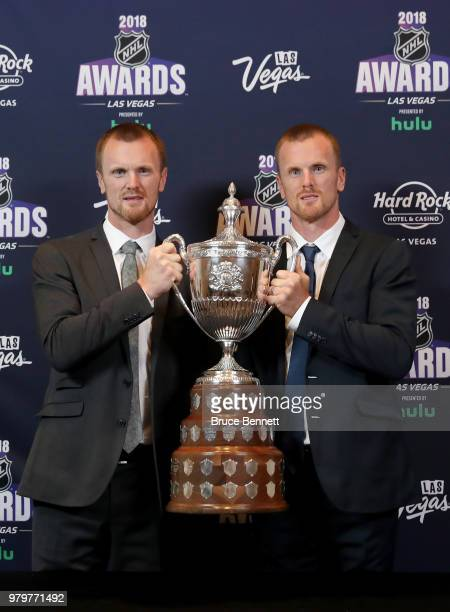 Henrik Sedin and Daniel Sedin of the Vancouver Canuks pose with the King Clancy Memorial Trophy in the press room at the 2018 NHL Awards presented by...