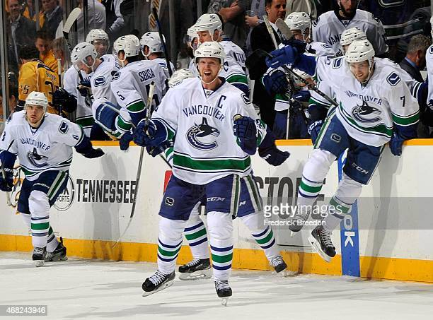 Henrik Sedin and Linden Vey of the Vancouver Canucks jump over the boards in celebration of a shootout victory over the Nashville Predators during...