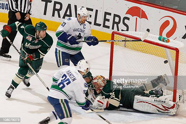 Henrik Sedin and the Vancouver Canucks narrowly miss a goal against Eric Nystrom, Greg Zanon, and goalie Anton Khudobin of the Minnesota Wild during...