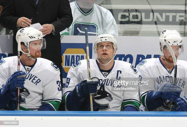 Henrik Sedin Markus Naslund and Daniel Sedin of the Vancouver Canucks look on from the bench area during their NHL game against the Edmonton Oilers...