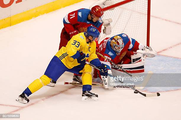 Henrik Sedin of Team Sweden tries to get a first period shot past Sergei Bobrovsky and Evgeni Malkin of Team Russia during the World Cup of Hockey at...