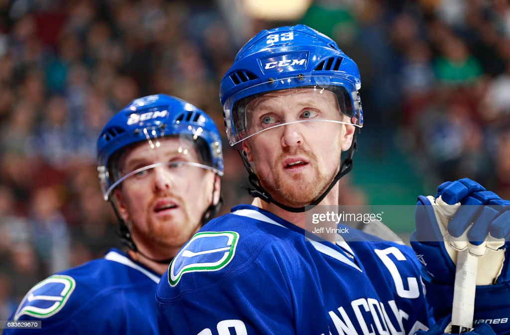 Henrik Sedin #33 of the Vancouver Canucks and Daniel Sedin #22 look on from the bench during their NHL game against the San Jose Sharks at Rogers Arena February 2, 2017 in Vancouver, British Columbia, Canada.