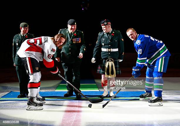 Henrik Sedin of the Vancouver Canucks and Erik Karlsson of the Ottawa Senators take a ceremonial faceoff celebrating Remembrance Day before their NHL...