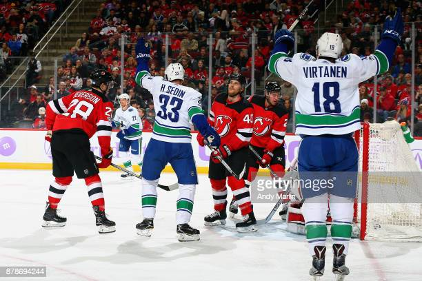 Henrik Sedin of the Vancouver Canucks and Jake Virtanen celebrate a goal by Daniel Sedin during the game against the New Jersey Devils at Prudential...