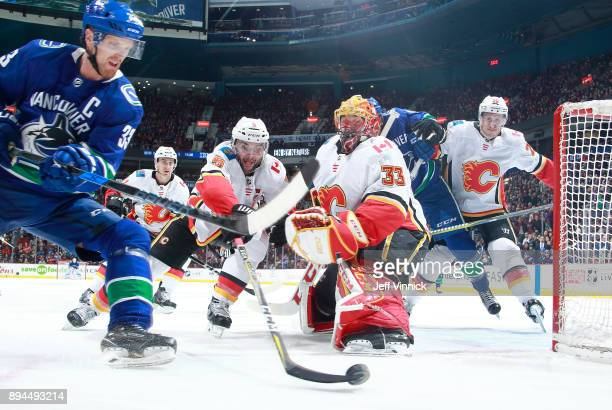 Henrik Sedin of the Vancouver Canucks and Mark Giordano of the Calgary Flames reach for the puck as David Rittich of the Calgary Flames makes a save...