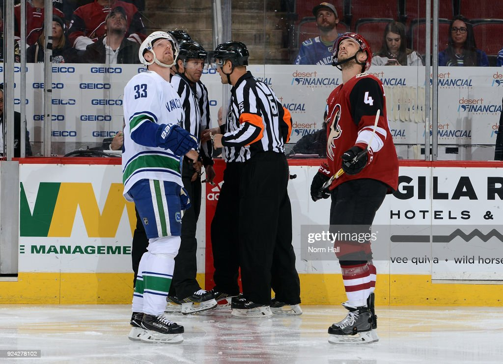 Henrik Sedin #33 of the Vancouver Canucks and Niklas Hjalmarsson #4 of the Arizona Coyotes look up at a video replay of a goal under review during the first period at Gila River Arena on February 25, 2018 in Glendale, Arizona.
