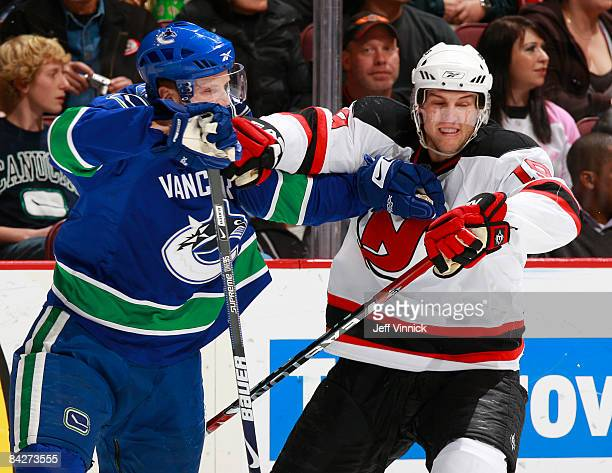 Henrik Sedin of the Vancouver Canucks and Travis Zajac of the New Jersey Devils keep each other in check during their game at General Motors Place on...