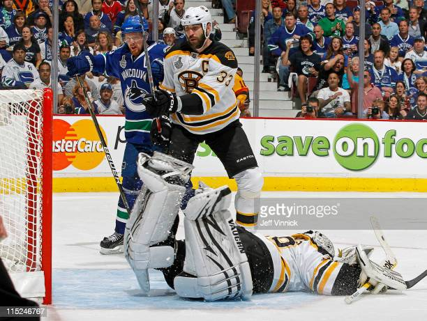 Henrik Sedin of the Vancouver Canucks and Zdeno Chara of the Boston Bruins watch Daniel Sedin of the Vancouver Canucks shot get past Tim Thomas of...