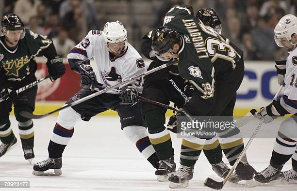 Henrik Sedin of the Vancouver Canucks battles for the puck with Joel Lundqvist of the Dallas Stars during game three of the 2007 NHL Western...
