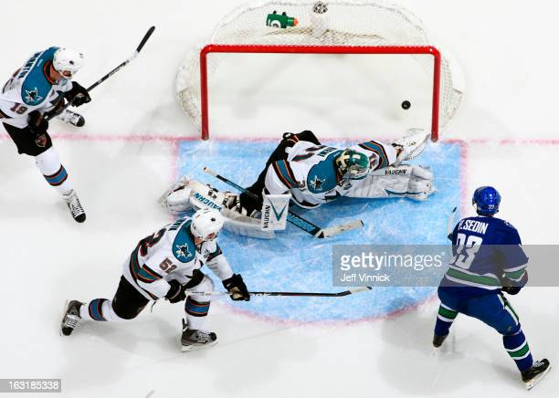Henrik Sedin of the Vancouver Canucks beats Antti Niemi of the San Jose Sharks for a goal while Matt Irwin and Joe Thornton of the Sharks watch...