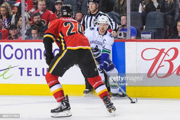 Henrik Sedin of the Vancouver Canucks carries the puck against Travis Hamonic of the Calgary Flames during an NHL game at Scotiabank Saddledome on...