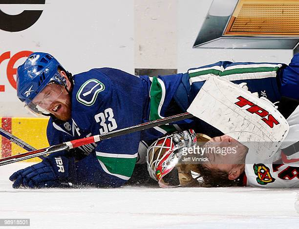 Henrik Sedin of the Vancouver Canucks collides with Antti Niemi of the Chicago Blackhawks in Game Four of the Western Conference Semifinals during...