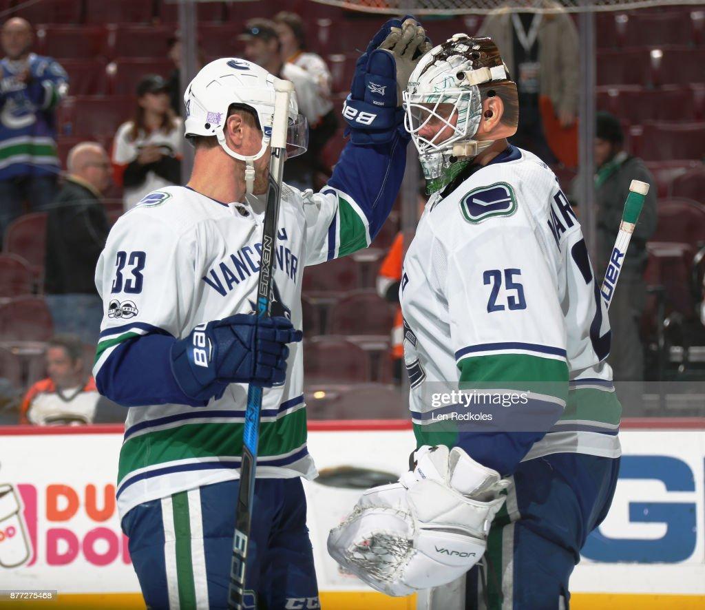 Henrik Sedin #33 of the Vancouver Canucks congratulates teammate Jacob Markstrom #25 after defeating the Philadelphia Flyers on November 21, 2017 at the Wells Fargo Center in Philadelphia, Pennsylvania. The Canucks went on to defeat the Flyers 5-2.