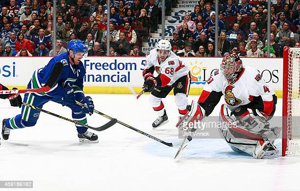 Henrik Sedin of the Vancouver Canucks Craig Anderson and Mike Hoffman of the Ottawa Senators eye the loose puck during their NHL game at Rogers Arena...
