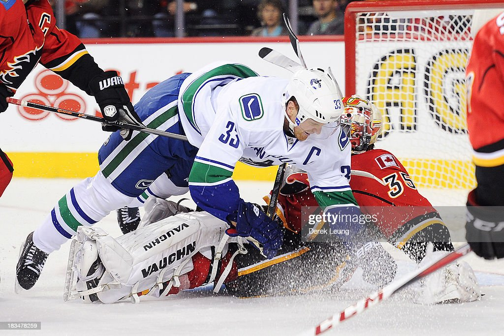 Henrik Sedin #33 of the Vancouver Canucks crashes into Joey MacDonald #35 of the Calgary Flames during the Flames' home opening NHL game at Scotiabank Saddledome on October 6, 2013 in Calgary, Alberta, Canada.