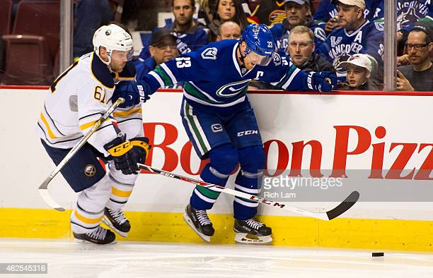 Henrik Sedin of the Vancouver Canucks fights through the check of Andre Benoit of the Buffalo Sabres along the side boards in NHL action on January...