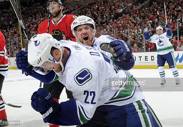 Henrik Sedin of the Vancouver Canucks grabs onto brother Daniel Sedin after Daniel scored on the Chicago Blackhawks as teammate Mikael Samuelsson...