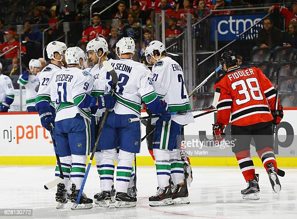 Henrik Sedin of the Vancouver Canucks is congratulated by his teammates after scoring a secondperiod goal as Vernon Fiddler of the New Jersey Devils...