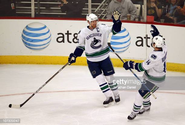Henrik Sedin of the Vancouver Canucks is congratulated by teammate Alexandre Burrows after scoring a 3rd period goal against the Chicago Blackhawks...