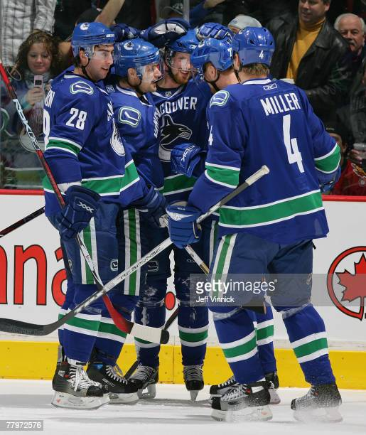 Henrik Sedin of the Vancouver Canucks is congratulated by teammates Daniel Sedin Markus Naslund Aaron Miller and Luc Bourdon after scoring against...