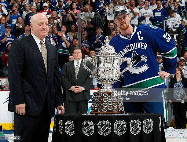Henrik Sedin of the Vancouver Canucks is presented the the Clarence S Campbell Bowl by NHL Deputy Commissioner Bill Daly after their 32 overtime win...