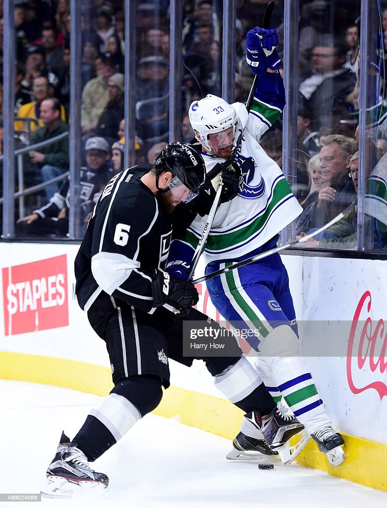 Henrik Sedin #33 of the Vancouver Canucks is taken off the puck by Jake Muzzin #6 of the Los Angeles Kings during the first period at Staples Center on December 1, 2015 in Los Angeles, California.