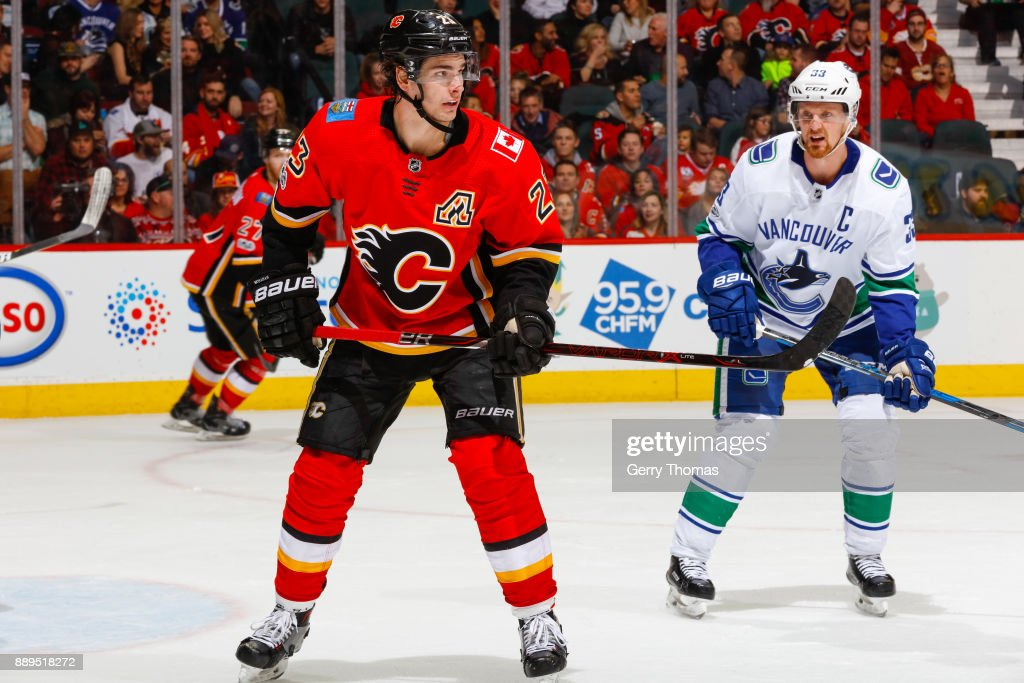 Henrik Sedin #33 of the Vancouver Canucks keeps an eye on Sean Monahan #23 of the Calgary Flames in a NHL game against the Vancouver Canucks at the Scotiabank Saddledome on December 09, 2017 in Calgary, Alberta, Canada.