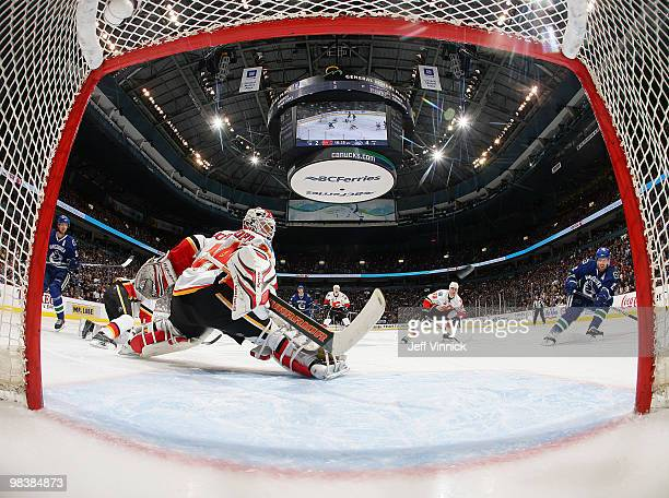 Henrik Sedin of the Vancouver Canucks looks on as Daniel Sedin of the Vancouver Canucks scores on Miikka Kiprusoff of the Calgary Flames during their...