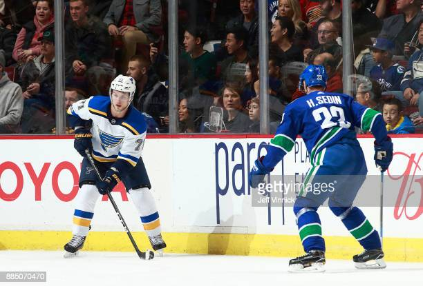 Henrik Sedin of the Vancouver Canucks looks on as Vladimir Sobotka of the St Louis Blues skates up ice with the puck during their NHL game at Rogers...