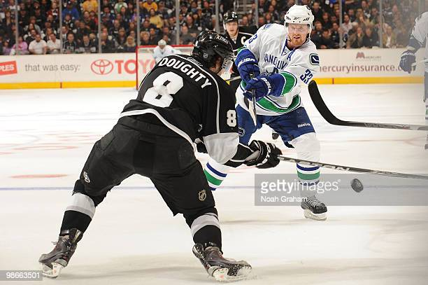 Henrik Sedin of the Vancouver Canucks passes the puck against Drew Doughty of the Los Angeles Kings in Game Six of the Western Conference...